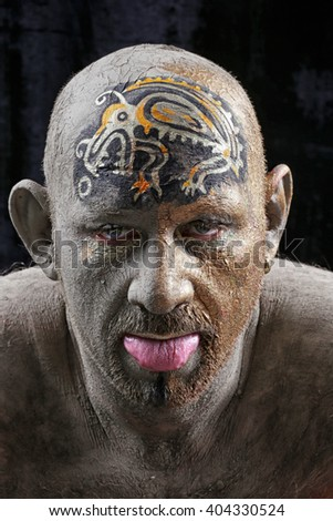 close-up portrait of a man in the clay body art, studio on a dark background - stock photo