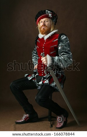 close-up portrait of a man of the Middle Ages with a beard and mustache in a suit isolated on a dark background with a sword sitting - stock photo