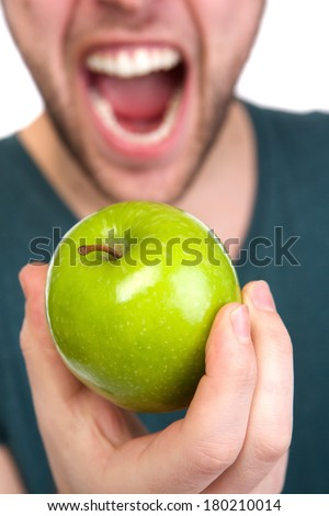 Close up portrait of a man with mouth open and green organic apple