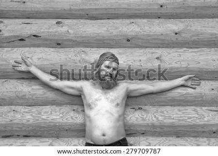 close-up portrait of a man with naked torso against the backdrop of a new log house in sunny spring day