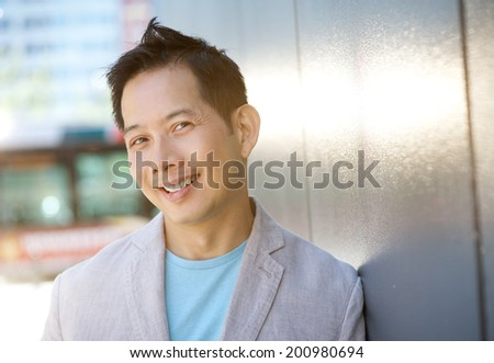Close up portrait of a mature asian man smiling outdoors - stock photo