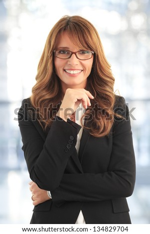 Close-up portrait of a mature business woman smiling in her office - stock photo