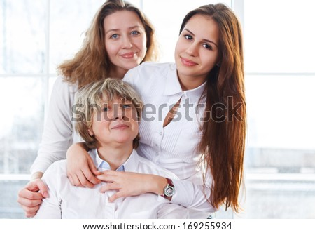 Close up portrait of a mature mother and adult daughter and teen granddaughter being close and hugging at home being happy and joyful  - stock photo