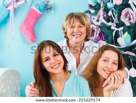 Close up portrait of a mature mother and adult daughter and teen granddaughter being close and hugging at home near the Christmas tree being happy and joyful - stock photo