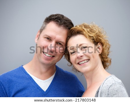 Close up portrait of a middle aged couple smiling against gray background - stock photo