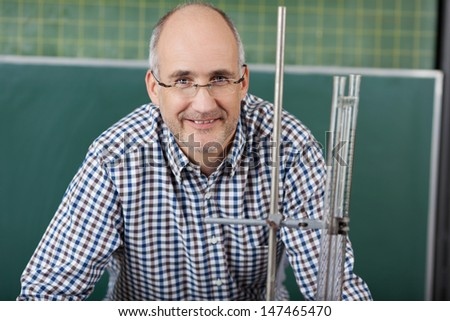 Close up portrait of a middle-aged male teacher in glasses giving physics lessons standing in front of a metal retort stand used in an experiment - stock photo