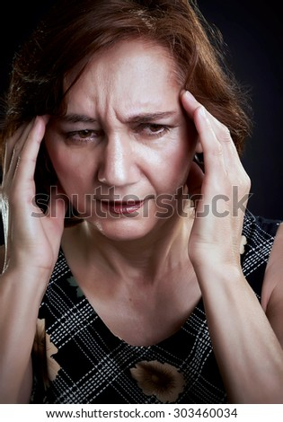 Close-up portrait of a middle aged woman with headache, massaging her forehead with both hands. Black background. - stock photo