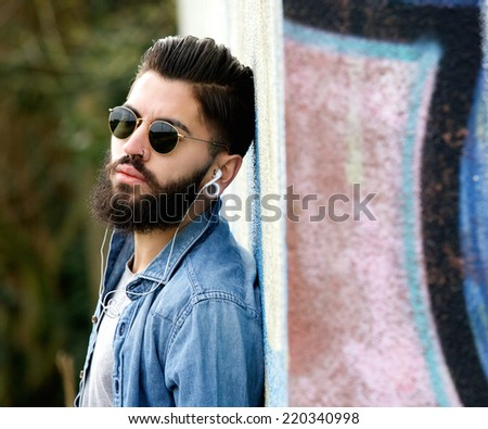 Close up portrait of a modern young man with beard listening to music with earphones - stock photo