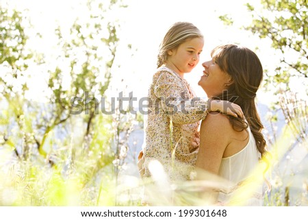 Close up portrait of a mother and daughter relaxing together in a beautiful spring field of long grass, hugging and enjoying a sunny holiday outdoors. Family love and holiday activities lifestyle. - stock photo
