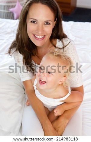 Close up portrait of a mother and little girl laughing together - stock photo