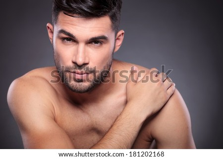 close-up portrait of a naked young man holding his hand on his shoulder and looking into the camera with a serious expression. on a black studio backgroud - stock photo