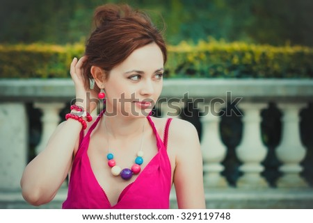 Close-up portrait of a nice young woman in the gardens of Paris - stock photo