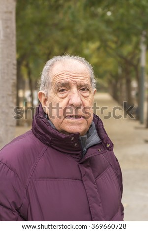 Close-up portrait of a older man in park - stock photo