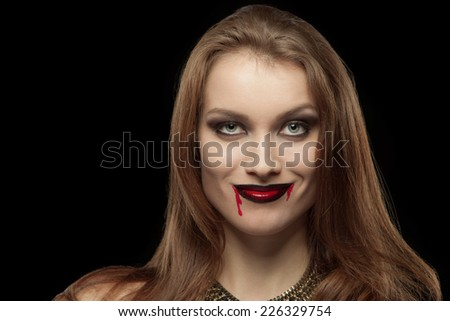Close-up portrait of a pale gothic vampire woman on a black background - stock photo