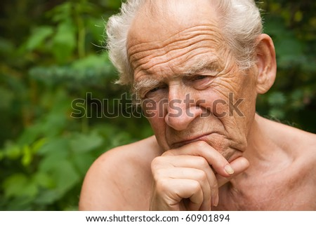 close-up portrait of a pensive senior man holding his hand near his face - stock photo