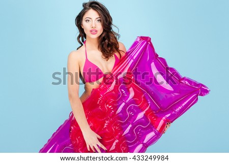 Close-up portrait of a pretty attractive beach girl with air mattress isolated on the blue background - stock photo