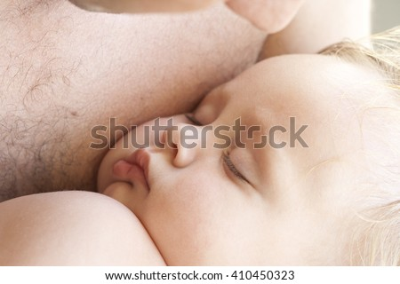 Close-up portrait of a pretty blond european toddler girl sleeping on her dad's chest. Close family relationships. Perfect facial features of an amazing kid. Happy childhood. Colorful photo