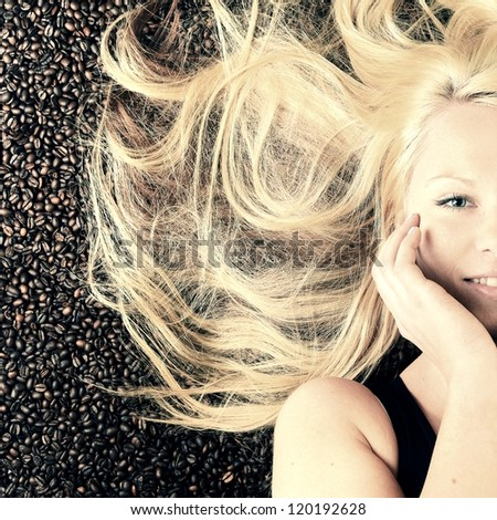 close up portrait of a pretty girl immersed in coffee beans - stock photo
