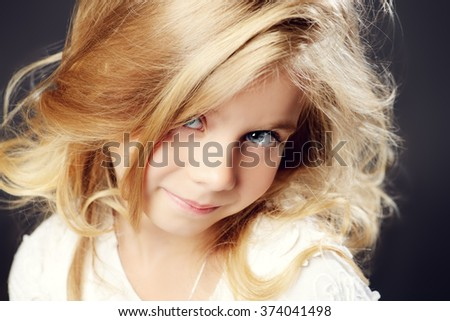 Close-up portrait of a pretty little girl with beautiful blonde hair wearing white dress. Studio shot. Kid's beauty, fashion. - stock photo