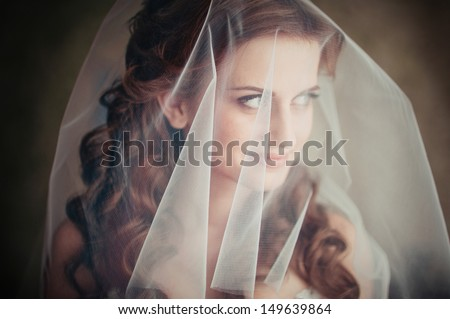 close-up portrait of a pretty shy bride with a veil - stock photo