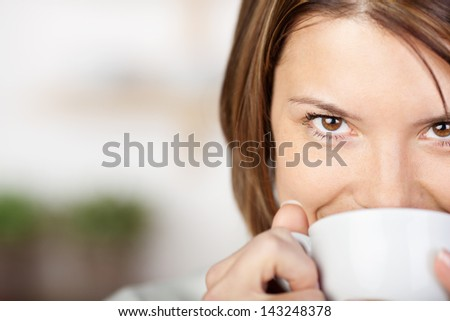 Close-up portrait of a pretty woman smiling and drinking coffee. - stock photo