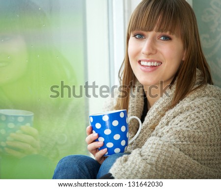 Close up portrait of a pretty woman smiling with cup of tea - stock photo