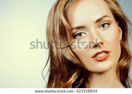 Close-up portrait of a pretty woman with beautiful long hair. Studio shot.