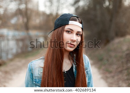 Close-up portrait of a pretty young woman in a black baseball cap and a denim jacket.