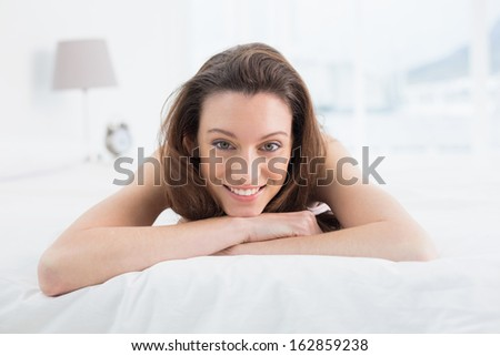 Close up portrait of a pretty young woman resting in bed at home