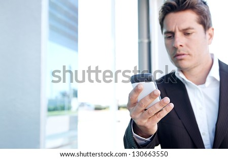"Close up portrait of a professional business man holding a ""smart phone"" and dialing while standing by a modern office building in the city. - stock photo"
