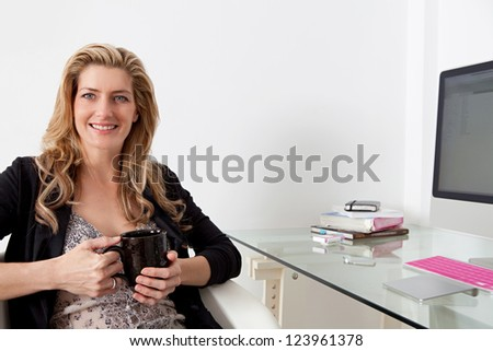Close up portrait of a professional woman working at her desk in her home office, holding a cup of hot beverage in her hands.