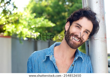 Close up portrait of a real happy man with beard smiling - stock photo