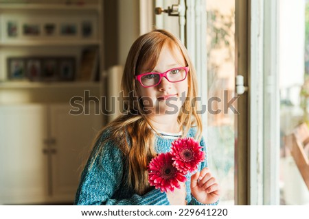 Close-up portrait of a red hair child girl in glasses - stock photo