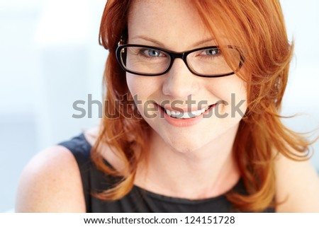 Close-up portrait of a red-haired beauty with a charming smile - stock photo