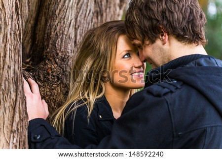Close up portrait of a romantic young couple standing next to a tree  - stock photo