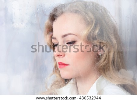 Close-up portrait of a sad beautiful woman near the window on a rainy day