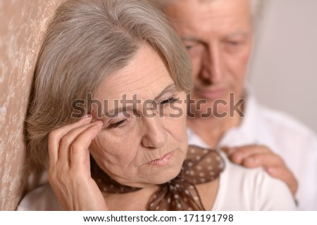 Close-up portrait of a sad elder couple on brown background
