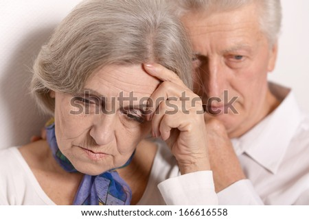 Close-up portrait of a sad elder couple on white background - stock photo
