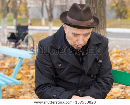 Close up portrait of a sad lonely old man on a park bench sitting with his head down and a despondent expression warmly dressed in a hat and overcoat against the chilly autumn weather - stock photo