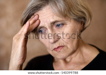 close-up portrait of a sad older woman on a beige background