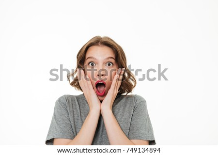 Close up portrait of a scrared pretty girl wearing make-up looking at camera and screaming isolated over white background