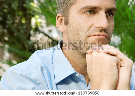 Close up portrait of a senior businessman sitting in a city park and holding his hands together under his chin, being thoughtful, outdoors. - stock photo