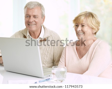 Close-up portrait of a senior couple in front of laptop