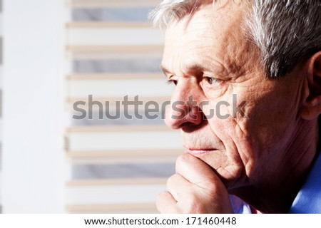 close-up portrait of a senior man thinking - stock photo