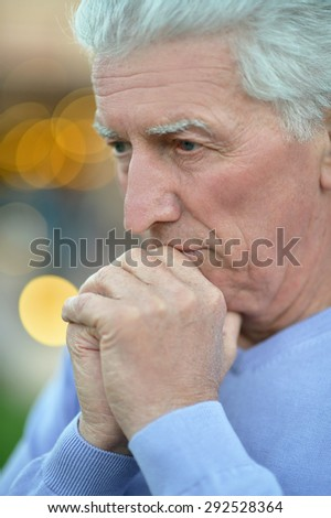 Close-up portrait of a senior man thinking about something - stock photo