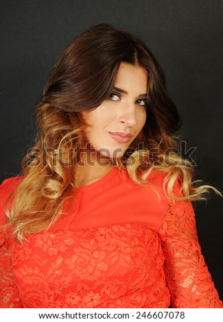 close up portrait of a sensual Young latin beautiful girl wearing a bright orange lace dress looking with an attitude away from the camera the camera isolated on black background - stock photo