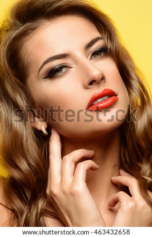 Close-up portrait of a sensual young woman with red lips over yellow background. Beauty, fashion. Cosmetics, make-up.