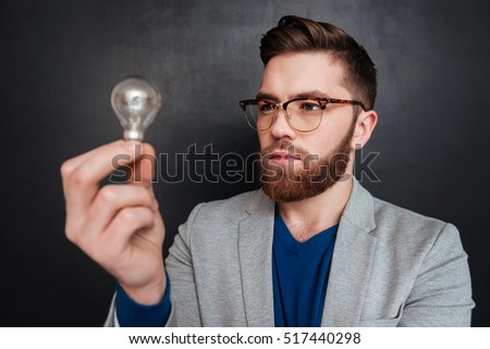 Close up portrait of a serious bearded young man standing and looking at light bulb over black backgorund