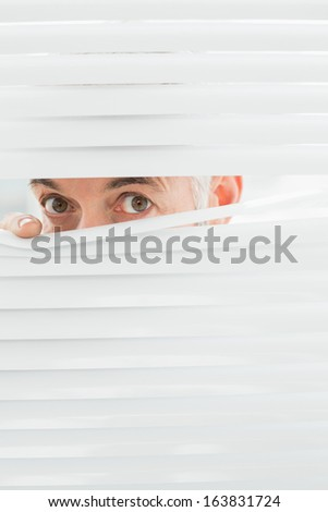 Close-up portrait of a serious mature businessman peeking through blinds in the office - stock photo