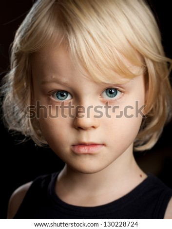 Close-up portrait of a serious young boy looking at camera. - stock photo